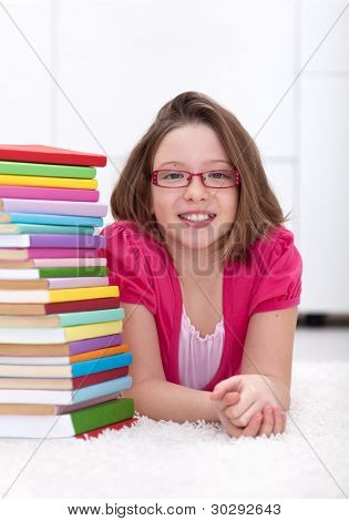 Young girl wearing glasses laying on the floor with lots of colorful books