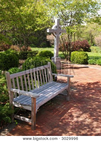An Empty Wood Bench By A Cross And Red Brick Patio