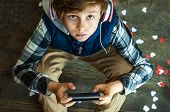 Fashionable Teenager Boy In Headphones And With A Mobile Phone Playing An Internet Game. The Depende poster