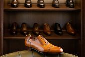 Brown full grain leather shoe in front of wooden display in men shoes boutique store. poster