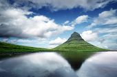 Picturesque landscape with Kirkjufell mountain, clear lake and cloudscape in blue sky poster