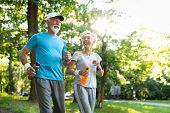 Mature Couple Jogging And Running Outdoors In Nature poster