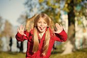 Girl Playful Grimace Face In Coat Enjoy Fall Park. Playful Kid Leisure. Child Blonde Long Hair Walki poster