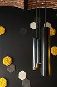 Black Wall With Decorative Orange And Yellow Honey Cell Of Moss And Loft Creative Lamp. In Interior  poster