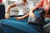 Couple packing their suitcases and take documents poster