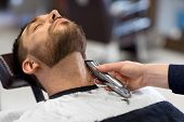 grooming and people concept - man and barber with trimmer or shaver cutting beard at barbershop poster