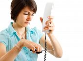 stock photo of stop hate  - Portrait of a stressed woman cutting a telephone cable - JPG