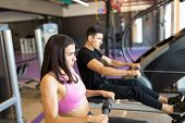 Determined Woman Exercising On Rowing Machine In Gym poster