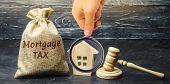 Money Bag With The Word Mortgage Tax, Judges Hammer And Wooden House. Mortgage Credit Lending. Tax  poster