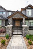 Entrance Of Luxury Residential House With Metal Gate And Stone Textured Walls. Big Family House Entr poster