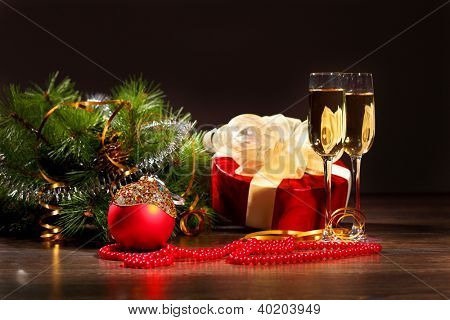New Year's still life with glasses of champagne. Decorations and ribbons on a bright color background