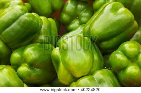 Green Bell Peppers at the farmers market with sharp focus on center vegetables
