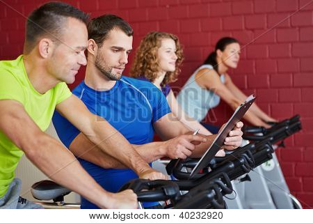 Fitness trainer with clipboard talking to a man on bike