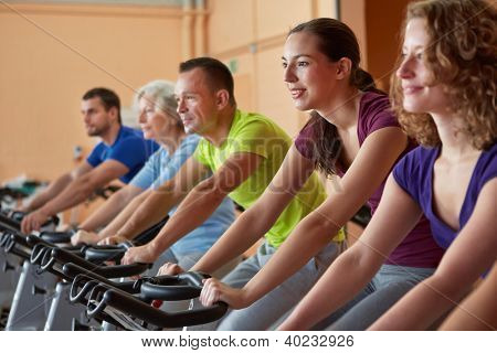 Mixed group riding bikes in class in fitness center