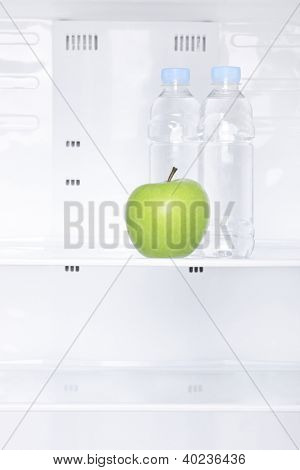 A green apple and bottles of mineral water in a fridge