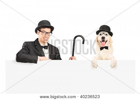 A performer in suit, retro hat and cane posing with dog behind a panel isolated on white