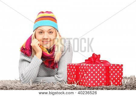 A smiling female with hat and neckwear lying on a carpet near gift isolated on white background