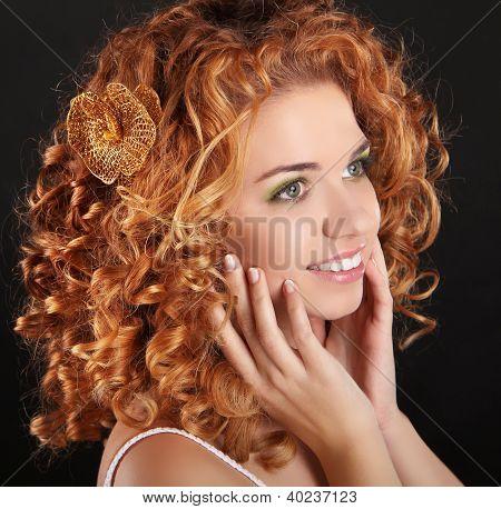 Menina sorridente atraente com cabelo encaracolado dourado sobre fundo escuro. Retrato da beleza.