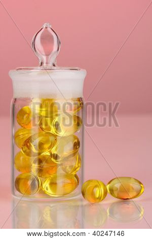 Capsules in receptacle on red background