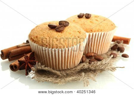 tasty muffin cakes on burlap, spices and coffee seeds, isolated on white