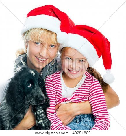 Beautiful mommy and little girl in Santa hats with dog on a white background