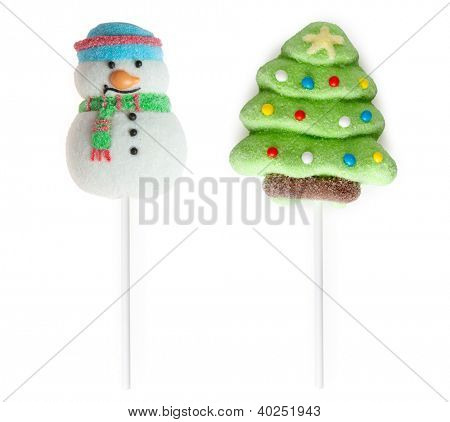 Candies: fir-tree and snowman on sticks on a white background