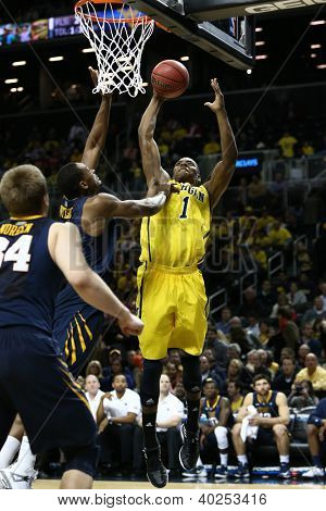 BROOKLYN-DEC 15: Michigan Wolverines forward Glenn Robinson III (1) shoots as West Virginia Mountaineers forward Dominique Rutledge (1) defends at Barclays Center on December 15, 2012 in Brooklyn.