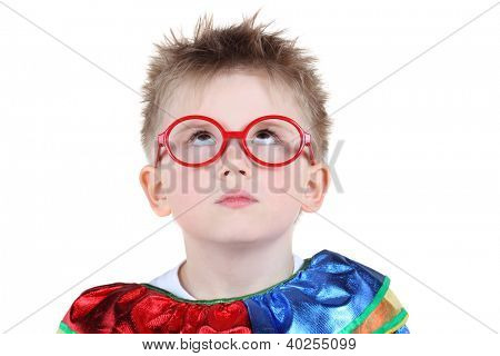 Little boy in big red glasses and clown costume looks up isolated on white background.