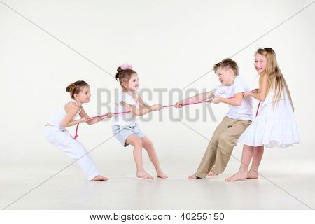 Four happy little boy and girls in white clothes draw over pink rope.