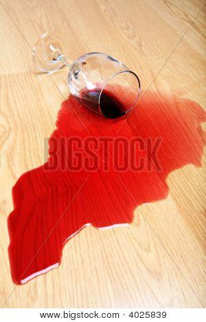 Derramamiento de vino en el piso de madera dura