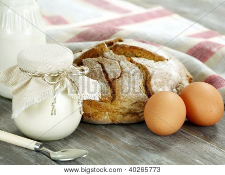 Homemade Yogurt, Milk, Bread And Eggs On A Wooden Table