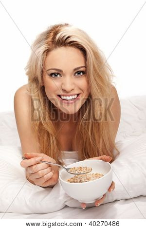 Beautiful relaxed young blonde woman enjoying a healthy breakfast of muesli or cereal as she lies on her bed facing the camera