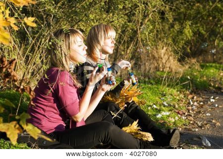 Two Young Women Starts Up Soap Bubble In Park