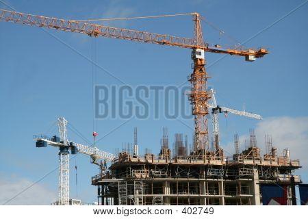 A Construction Site With A Yellow Crane And A White Crane