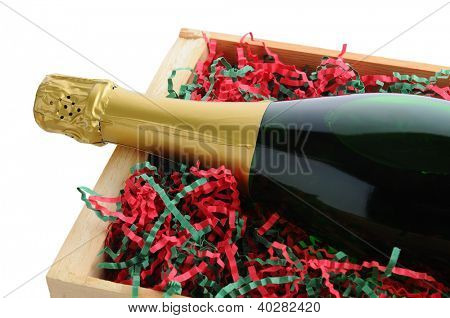 Closeup of a Champagne bottle in a wood shipping crate with shredded filler paper in Christmas Holiday colors. Horizontal format isolated on a white background.