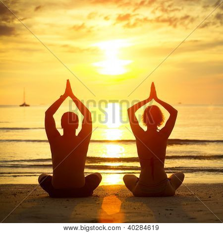 Young couple practicing yoga on the beach at sunset