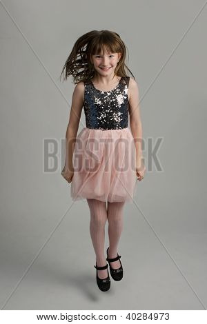 Happy girl wearing elegant dress jumping, studio shot