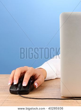 woman's hands pushing keys of pc mouse, on blue background close-up