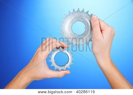 Man holding metallic cogwheels in his hands on blue background