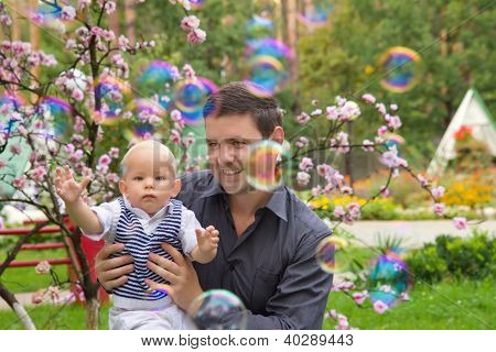 Father And His Child Playing With Soap Bubbles