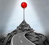 image of goal setting  - Achieving your goals and following the difficult challenging path to success with a mountain of tangled roads and highways leading to the top with a location red pushpin as a symbol of determination - JPG