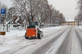 stock photo of bobcat  - small excavator bobcat working on the street cleaning snow - JPG