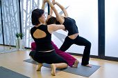 stock photo of yoga instructor  - two women doing yoga exercise indoors in studio - JPG