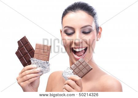 Chocoholic young woman holding three chocolate bars in hand, smiling.
