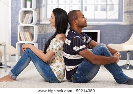 Happy interracial couple sitting on floor back-to-back, daydreaming, smiling.