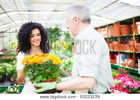 Portrait of a smiling greenhouse worker giving a flower pot to a customer