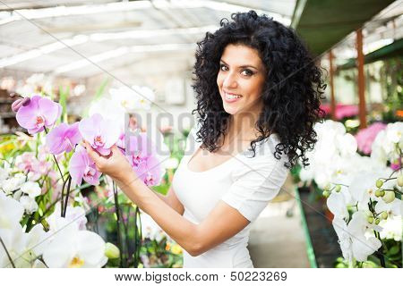 Woman looking to flowers in a greenhouse
