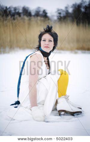 Woman Wearing A Stylish Dress, Scarf And Ice Skates Sitting On A Frozen Lake.