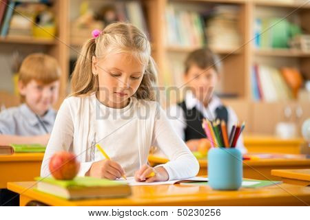 Little schoolgirl sitting behind school desk during lesson in school