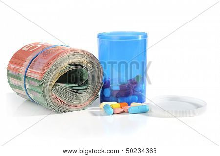 Extreme close-up image of tablets and container with roll of money